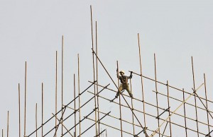 A labourer installs scaffolding at a construction site in Shenyang